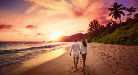 Młodzi kochankowie szczęśliwy na plaży. Para spacerująca w romantycznej podróży Miesiąc miodowy Wakacje Summe Holidays Romans Zachód słońca