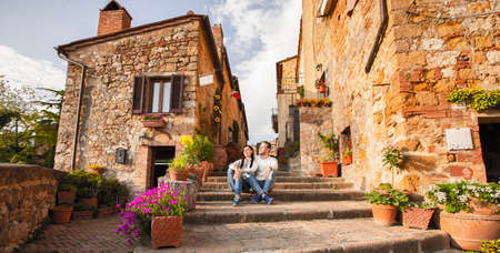 Beautiful Tourist Couple In Love Enjoying Rest In The Old City At Sunset. Happy Young Man And Woman Travel Concept