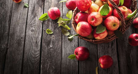 Fresh Red Apples With Green Leaves On A Wooden  Background. Top view Stockfoto