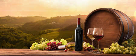 Bottles And Wineglasses With Grapes And Barrel On A Sunny Background. Italy Tuscany 스톡 콘텐츠 - 129598750