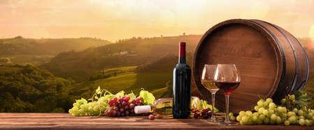 Flessen En Wijnglazen Met Druiven En Vat Op Een Zonnige Achtergrond. Italië Toscane