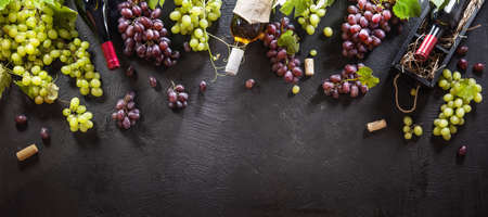 Red And White Grapes With Bottles On A Black Background. Top View Stockfoto