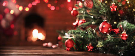 Christmas Tree with Decorations Near a Fireplace with Lights Stockfoto