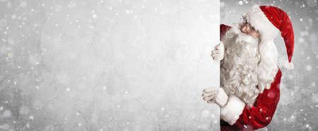 Babbo Natale che tiene il fondo dell'insegna della pubblicità in bianco con lo spazio della copia Archivio Fotografico