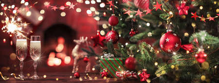 Christmas Tree with Decorations and Champagne Near a Fireplace with Lights  Stockfoto