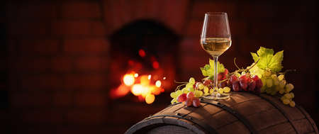 White Wine and Grapes on the Background of the Fireplace