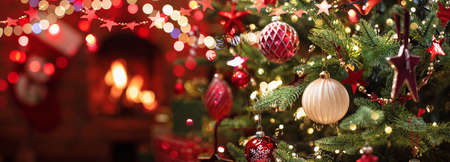 Christmas Tree with Decorations Near a Fireplace with Lights Standard-Bild