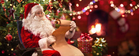 Santa Claus Sitting at His Room at Home Near Christmas Tree and Reading Christmas Letter or Wish List
