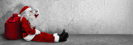 Sitting Santa Claus With A Bag. Christmas and New Year Concept Standard-Bild