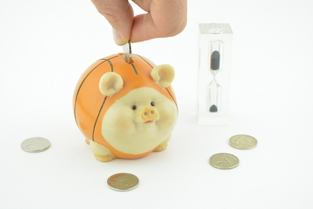 Money box as pig and time clock. Orange thrift-box for money with hourglass. Save your money in special box for coins. Russian ruble in money box. Hand puts coins to money box