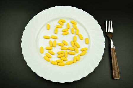 Yellow pills lying on a white plate with silver fork.  Medical overuse, tablet addiction Stock Photo