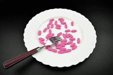 erection: Pink pills lying on the white plate with a spoon. Love pills concept.
