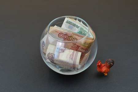 next year: Russian rubles in glass vase and cock. Cock is a symbol of next year. Money and cock