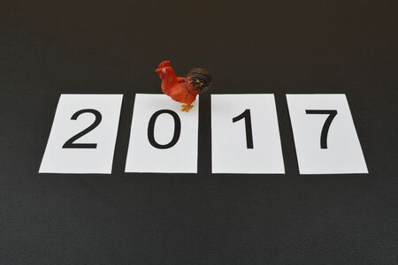 next year: Next year symbol. Text 2017 and cock stands on black background