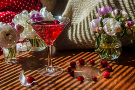Rustic still life with glass of red drink with autumn berries surrounded by white flowers on a textile background on a wooden table in the diagonal striped shadow of the blinds . Bright sunny day. Фото со стока