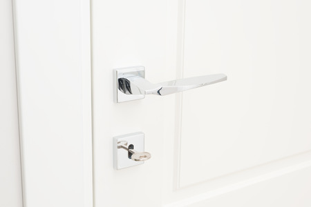 Modern glossy chrome door handle and keyhole with key. Close-up elements of the interior of the apartment
