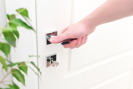 Male hand with modern chrome door handle. Close-up elements of the interior of the apartment. White door and the key in the keyhole. Green leaves plants