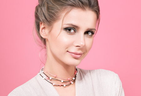 Closeup portrait of in pink. Beautiful young woman in a light blouse on a pink background. Beads or decoration on the neck. Hairstyle and professional makeup. A gentle smile, stylish appearance Stock Photo