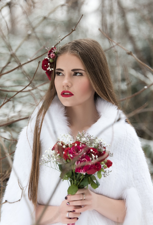Portrait of the bride in the winter forest. White fur coat, a bouquet of flowers in hand