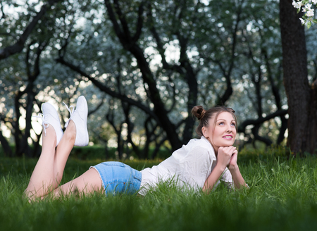 Beautiful young woman lying in the park on the grass, thinking about something or dreaming. Legs lifted up. White sneakers, short shorts. Hairstyle and light makeup. Spring mood