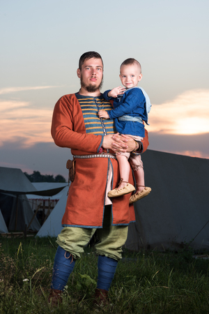 Vertical portrait of a Slavic man with a baby in historical costume. The image of a man from the past. Vintage clothing. A father and his son. The sunset in the background