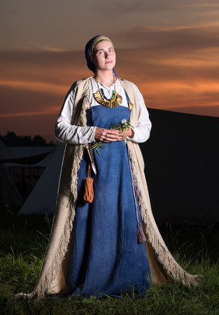 Vertical portrait in full growth of Slavic women from the past. Historical reconstruction. National vintage clothing. The sunset in the background Stock Photo