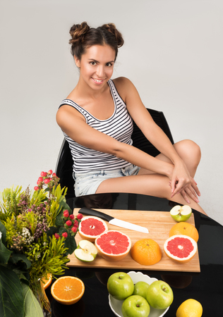 Healthy eating. Vertical portrait of a beautiful young woman at the table. Sliced fruit on the table. The stylish appearance of the model, makeup and hairstyle. A neutral grey background Stock Photo