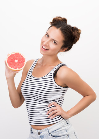 Joyful young woman holding a grapefruit. Striped tank top. Healthy, natural food. White background Stock fotó