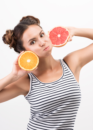 Cheerful young woman with citrus fruit, put to the face. Cheerfulness and good mood. Striped tank top and hairstyle. Neutral white background