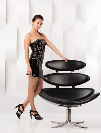 Young beautiful woman in evening dress stands near modern chairs and holds it to the back. Stylish in appearance. White wall with a wavy texture in the background