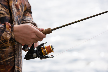 A fisherman catches a fish. Hands of a fisherman with a spinning rod in hand closeup. Spin fishing reel Archivio Fotografico