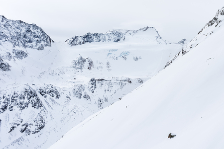 Snow-covered mountain slope. The Alpine landscape. High mountains and glacier in the background