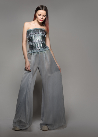 Fashion model in full length. Glamour Woman in wide-leg pants. A neutral grey background