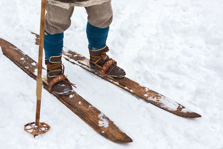 Male feet ancient skier and vintage skis. Historical reconstruction. Leather ski boots and wooden skis