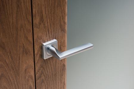 Close-up of steel door handle on interior door. Dark oak and frosted glass.