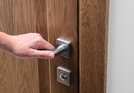 The man opens the door. Close - up of hand and door handle. Dark solid oak door.