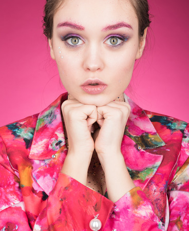 Portrait of sympathetic young woman in a bright colorful jacket. Makeup with glitter. Pink background 免版税图像