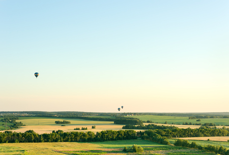 Flying in a balloon over the fields. Cloudless summer day. Free space