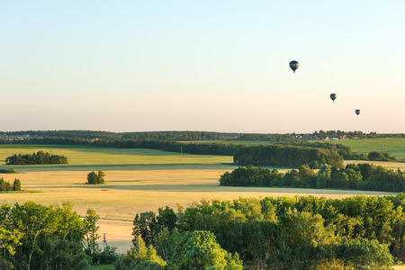 Three air balloons flying over the fields
