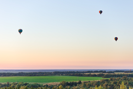 Flying in a balloon. Three objects in the air against a cloudless sky. Evening landscape