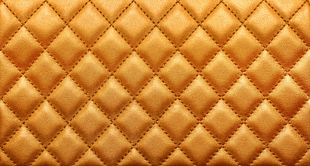 Close-up texture of genuine leather with rhombic stitching. Rich gold color. Luxury background