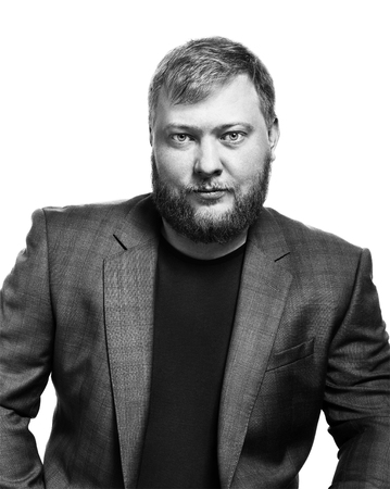Black and white portrait of a bearded man. Office style, jacket and t-shirt. Isolated on white background