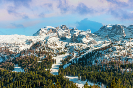 Beautiful  winter Alpine landscape. Snow and mountain peaks. Ski slopes and forest
