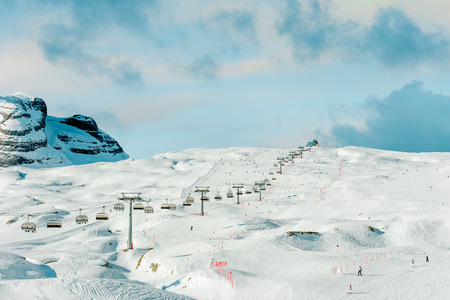 Winter ski holidays. Alpine landscape. Snow and mountain peaks. Ski slopes and cable car