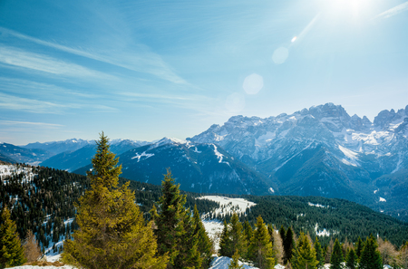 Beautiful winter Alpine landscape. Bright sun, snow-capped peaks and spruce forest. Holidays in the mountains