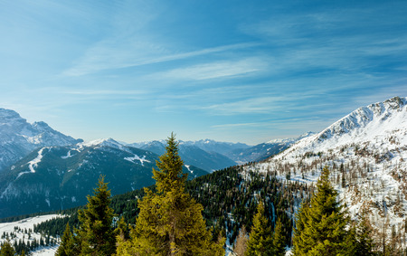 Beautiful winter Alpine landscape. Bright sun, snow-capped peaks and spruce forest. Rest in mountains Reklamní fotografie