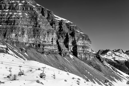 Black and white landscape. Cable car to sky resort. Massive rocks and mountains on the horizon. Winter holidays in the Alps