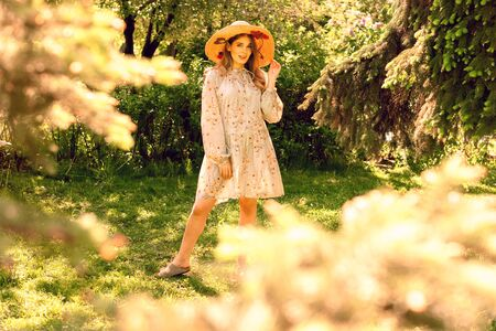 Beautiful young woman posing in the Park. Hat and light summer dress. Clearing in the forest Reklamní fotografie