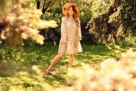 Beautiful young woman in the Park. Hat and light summer dress. Clearing in the forest Reklamní fotografie