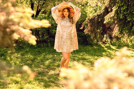 Beautiful young woman in the forest. Hat and light summer dress. Summer mood
